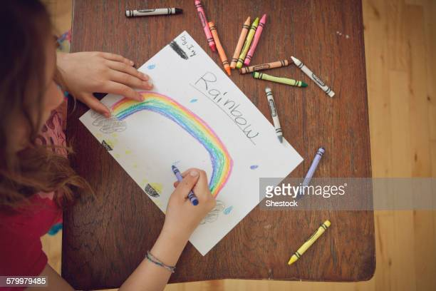 Caucasian girl drawing rainbow with crayons on table