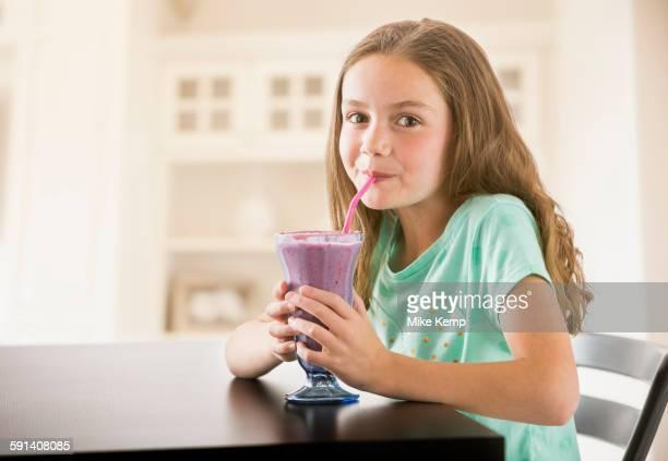 Caucasian girl drinking milkshake in kitchen
