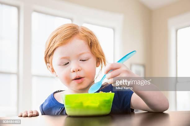 Caucasian girl eating at table