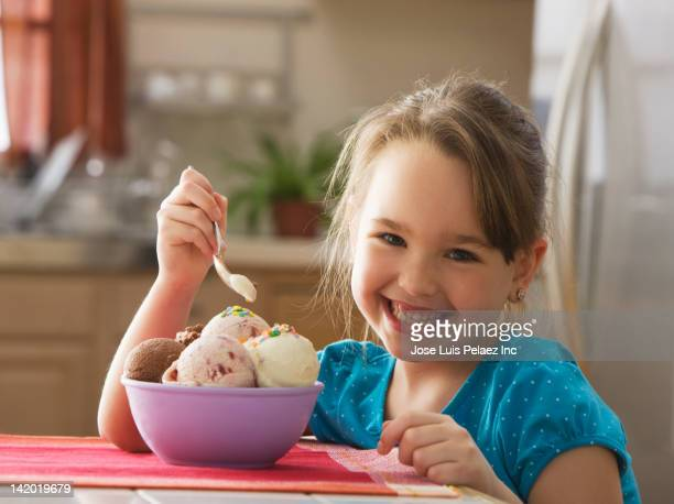 caucasian girl eating bowl of ice cream - solo una bambina femmina foto e immagini stock