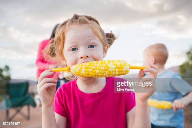Caucasian girl eating corn on the cob