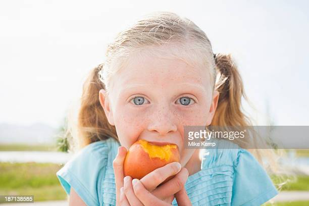 Caucasian girl eating fruit outdoors