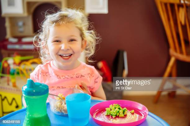 Caucasian girl eating in high chair