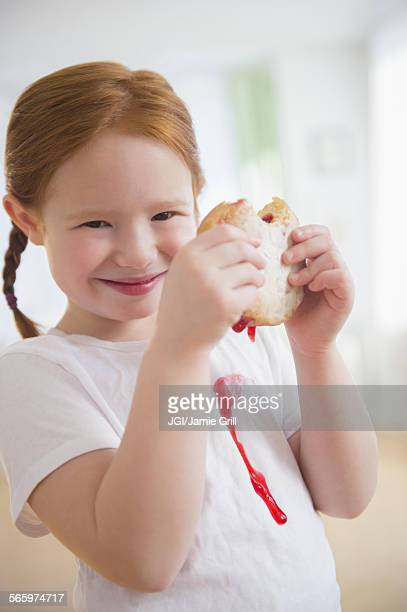 Caucasian girl eating messy jelly donut