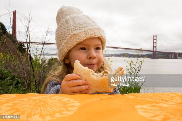 Caucasian girl eating sandwich outdoors