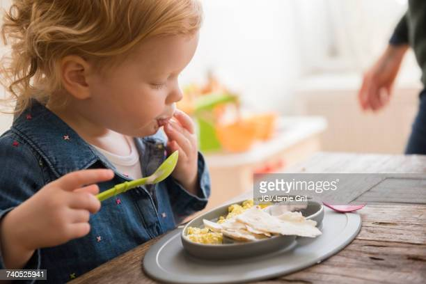 Caucasian girl eating with fingers and spoon