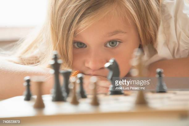 caucasian girl examining chess game board - chess stock pictures, royalty-free photos & images