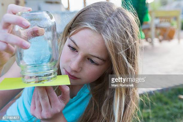 Caucasian girl examining insects in jar