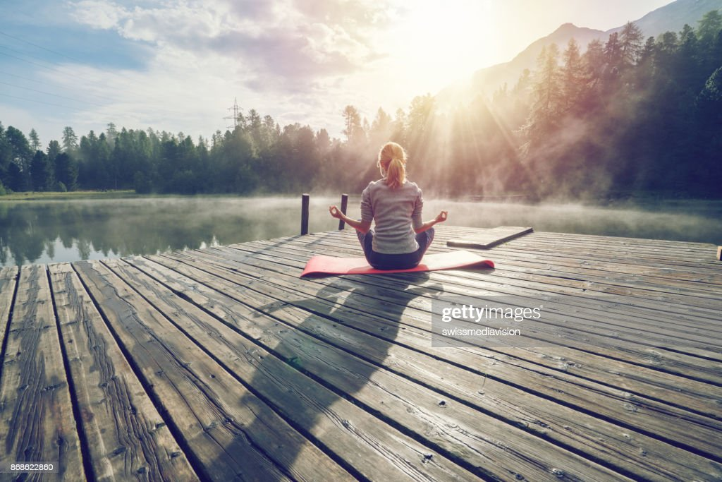 Caucasian girl exercising yoga in nature, morning by the lake in Switzerland : Stock Photo