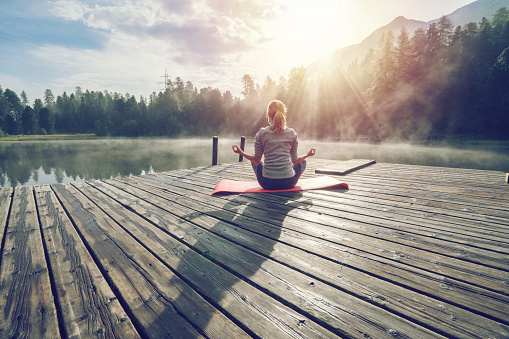 Caucasian girl exercising yoga in nature, morning by the lake in Switzerland 868622860