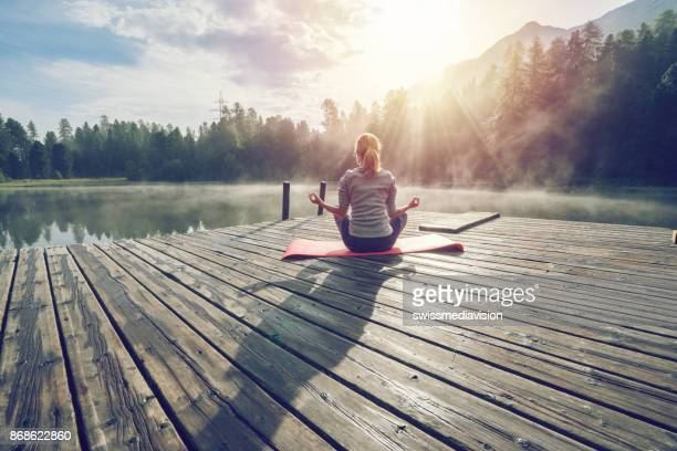 caucasian girl exercising yoga in nature, morning by the lake in switzerland - gente serena foto e immagini stock