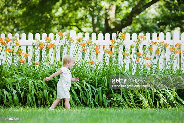 caucasian girl exploring flowers in backyard - hek stockfoto's en -beelden