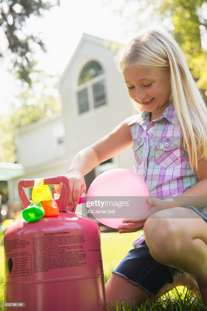 Caucasian girl filling balloons outdoors : Foto stock