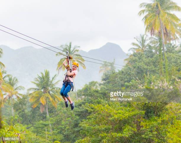 caucasian girl hanging on zip line in forest - st. lucia stock pictures, royalty-free photos & images