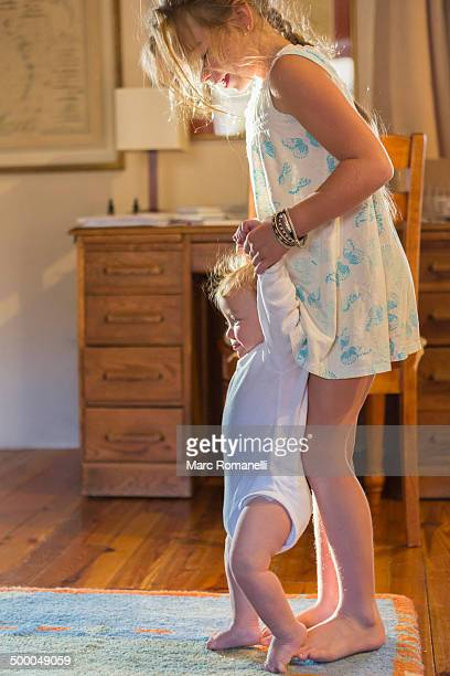 Caucasian girl helping baby walk