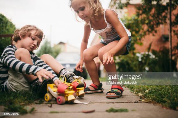 Caucasian girl helping boy with rollerskates