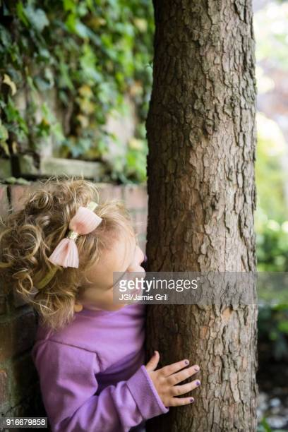 Caucasian girl hiding behind tree trunk