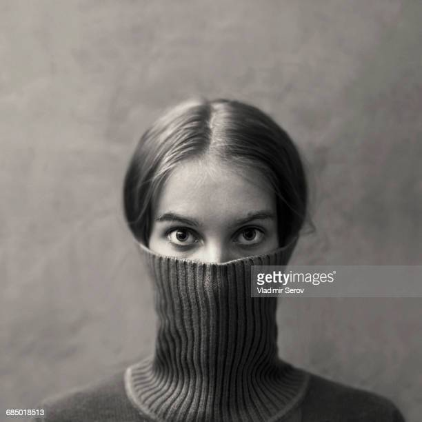 Caucasian girl hiding face in turtleneck