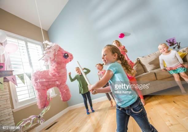 Caucasian girl hitting pinata at party