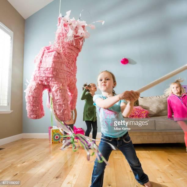 caucasian girl hitting pinata at party - pinata stock pictures, royalty-free photos & images