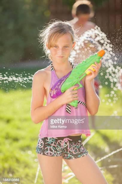 caucasian girl holding a water gun - tween girls hot stock photos and pictures