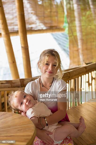 Caucasian girl holding baby sibling