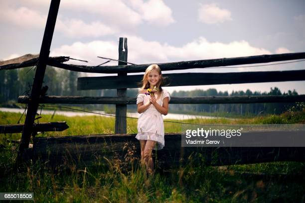 Caucasian girl holding bouquet of wildflowers leaning on wooden fence