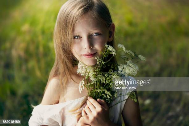 Caucasian girl holding bouquet of wildflowers