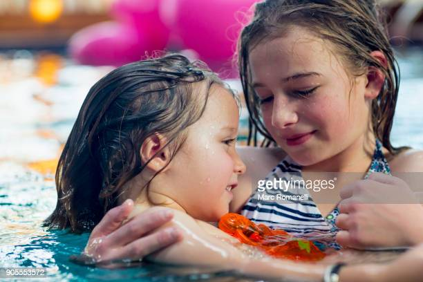 Caucasian girl holding brother in swimming pool