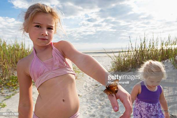 Caucasian girl holding butterfly on beach
