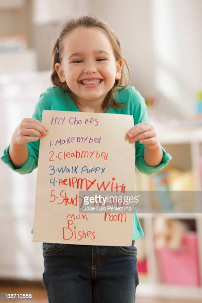 Caucasian girl holding chore list in bedroom
