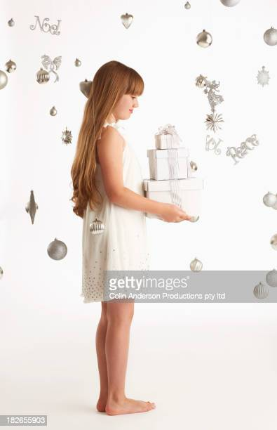 Caucasian girl holding Christmas gifts