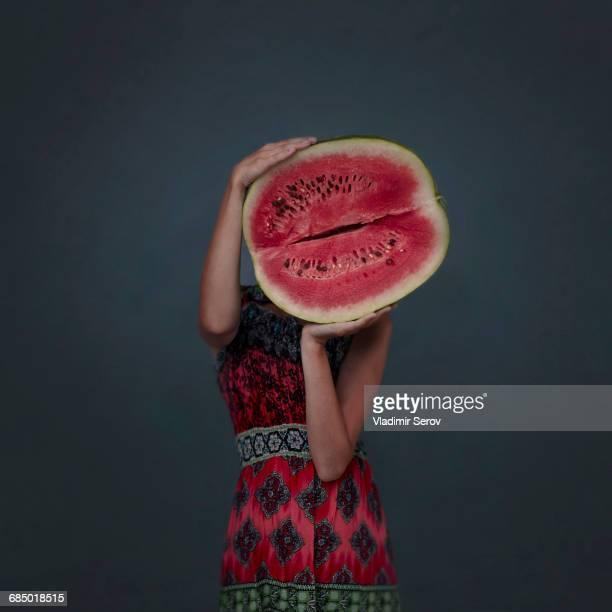 Caucasian girl holding enormous sliced watermelon