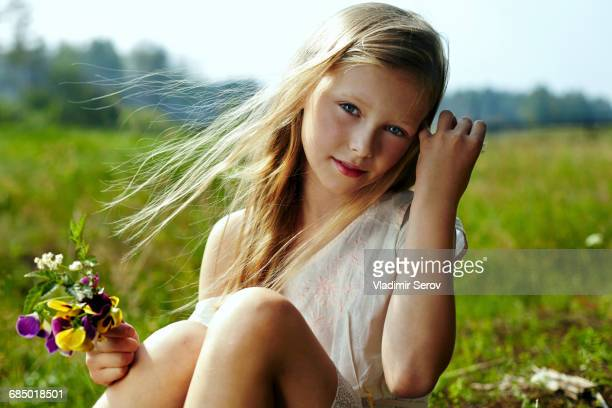 Caucasian girl holding flowers in windy field