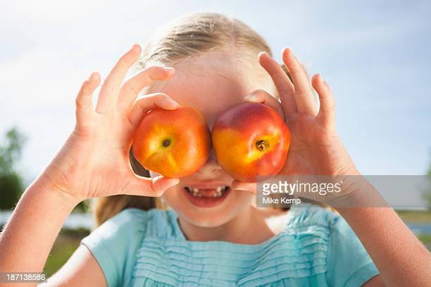 Caucasian girl holding fruit over eyes