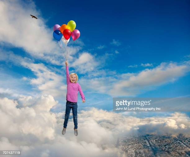 Caucasian girl holding helium balloons flying in clouds over cityscape