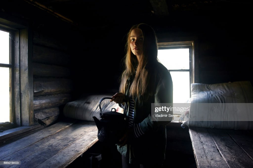 Caucasian girl holding kettle in log home