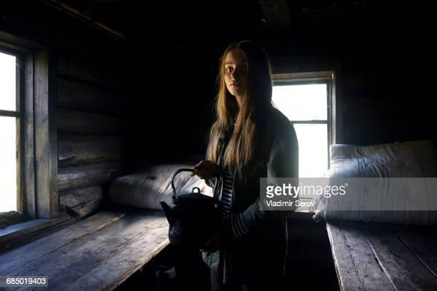 Caucasian girl holding kettle in log home