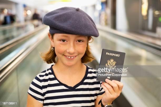 caucasian girl holding passport in airport - ベレー帽 ストックフォトと画像