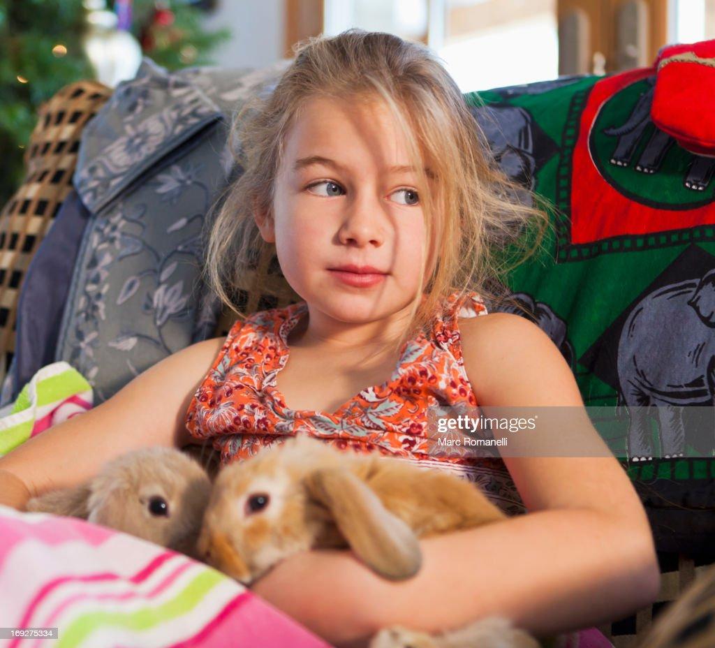 Caucasian girl holding pet rabbits on sofa : Stock Photo