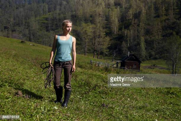 Caucasian girl holding rope on hill
