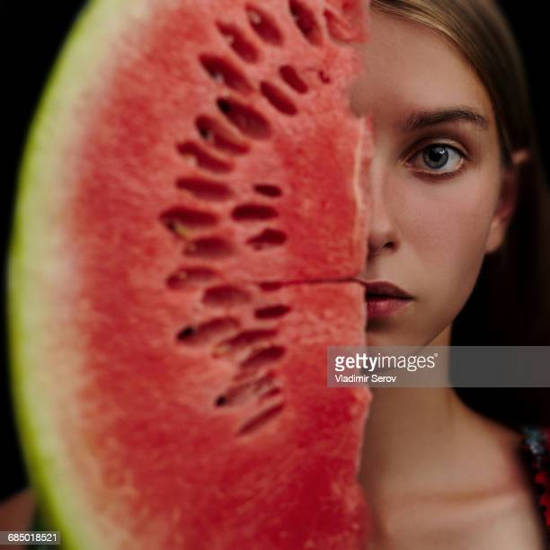 Caucasian girl holding slice of watermelon over half of face