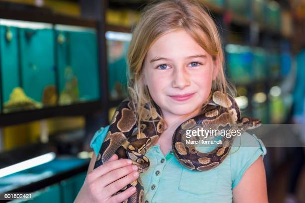 Caucasian girl holding snake in pet store
