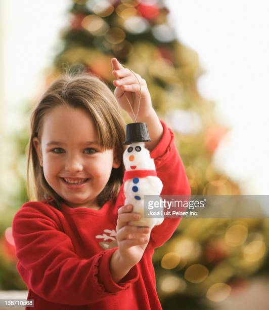 Caucasian girl holding snowman Christmas ornament