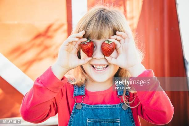 Caucasian girl holding strawberries over eyes