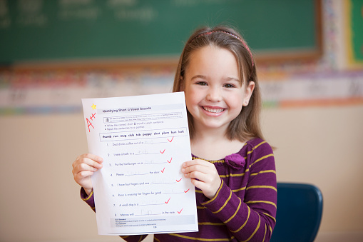 Caucasian girl holding test with an A+ - gettyimageskorea