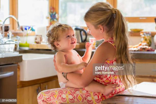 Caucasian girl holding toddler brother in kitchen