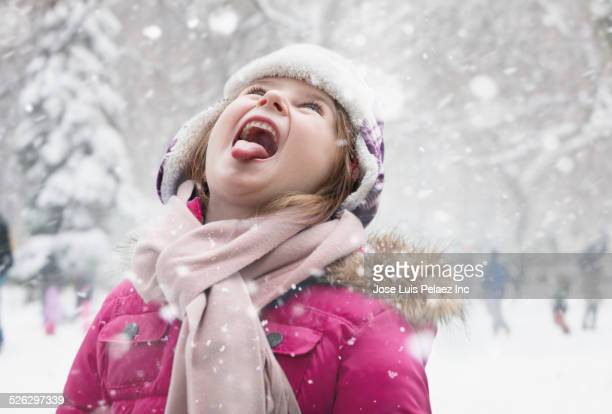 Caucasian girl holding tongue out in snow