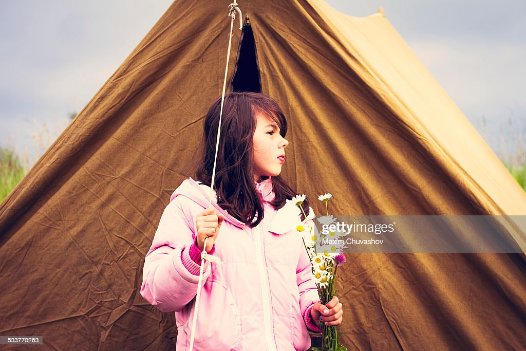 Caucasian girl holding wildflowers near camp tent : Foto stock