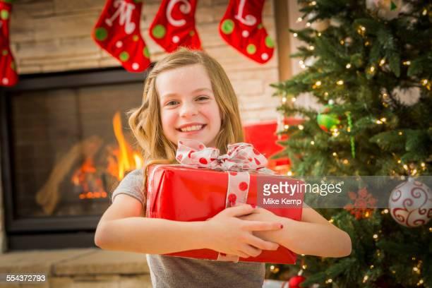 Caucasian girl hugging Christmas gift